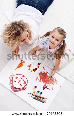 Painting with mom - little girl with brush and colors - stock photo