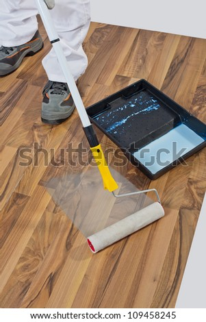 painting with primer wooden floor for waterproofing - stock photo
