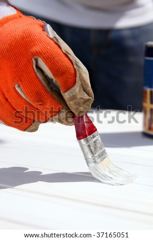 Painting wooden boards with white protective paint with a brush. Do it yourself, DIY - stock photo