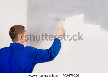 painting work, builder man paints the wall - stock photo