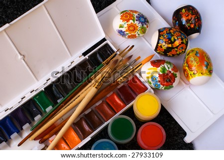 Paints, brushes and easter eggs on a palette - stock photo