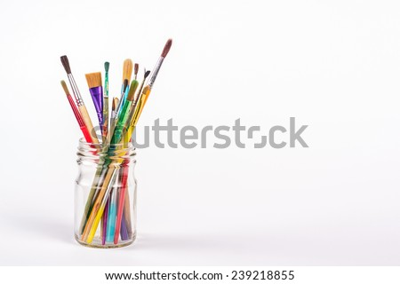 paints brushes in a glass isolated on white background - stock photo
