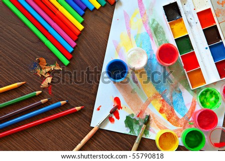Paints, pencils and brushes on wooden to a floor - stock photo