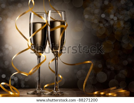 Pair glass of champagne. New year celebration or wedding concept theme. Paper streamer with defocused lens blur over background. Celebration concept. - stock photo