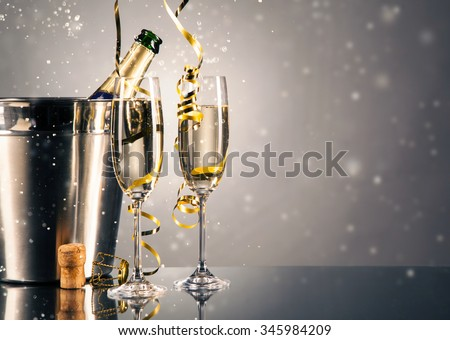 Pair glass of champagne with bottle in metal container. New Year celebration theme with blur spots of bubbles - stock photo