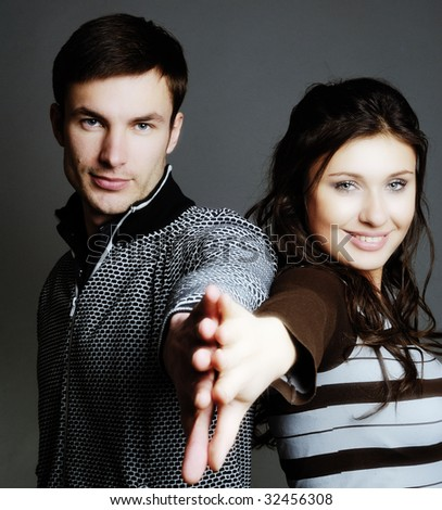 Pair nice young people on  dark background,  portrait - stock photo