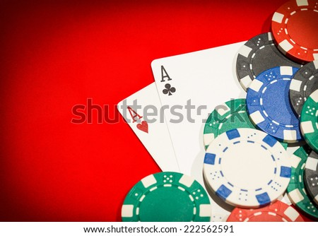 Pair of aces and chips on a red table - stock photo