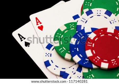 Pair of aces and poker chips isolated on black background