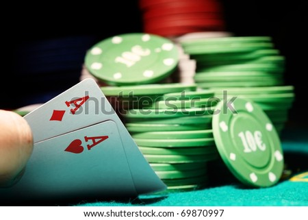 Pair of aces and poker chips on a green table in casino - stock photo