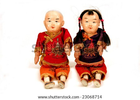 Pair of antique Asian dolls, boy and girl, on white background - stock photo