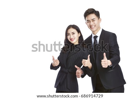 pair of asian business people in formal wear showing two-thumb-up sign, looking at camera smiling, isolated on white background.