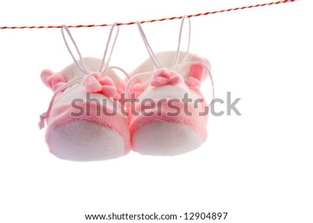 Pair of baby's slippers hanging on a rope. Including copy space. - stock photo