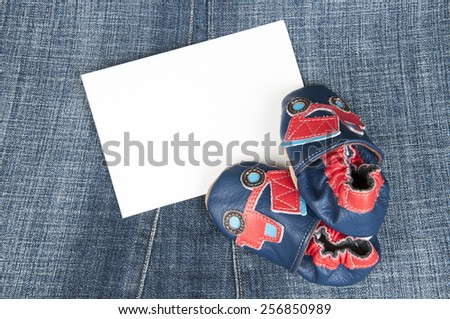 pair of baby shoes on jeans - stock photo