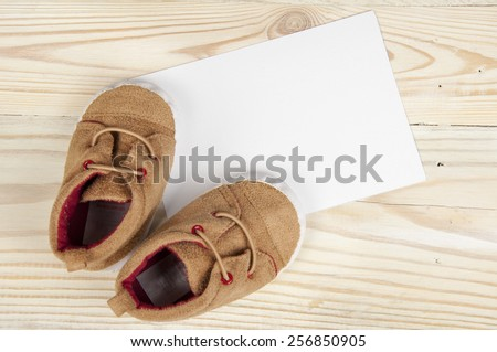 pair of baby shoes on wooden table - stock photo