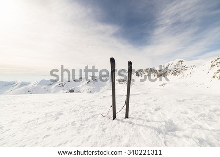 Pair of back country ski on the mountain summit. Stunning panoramic view of the alpine arc with clouds covering the valleys below. Concept of success and conquering the top. - stock photo