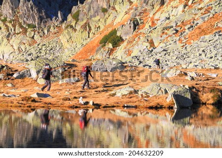 Pair of backpackers reflected by glacier lake - stock photo