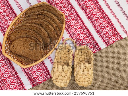 Pair of bast shoes and a piece of rye bread on folk embroidered tablecloths - stock photo