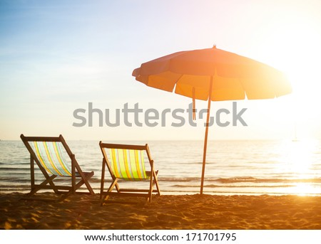 Pair of beach loungers on deserted coast sea at sunrise. - stock photo