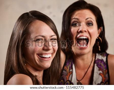 Pair of beautiful Caucasian brunette women laughing - stock photo