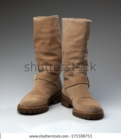 Pair of beige suede fashionable winter boots. Creative.
