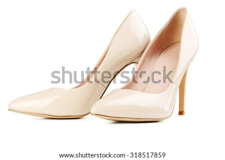 Pair of beige women's high-heeled shoes isolated on a white - stock photo