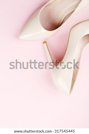 Pair of beige women's high-heeled shoes on pink background - stock photo