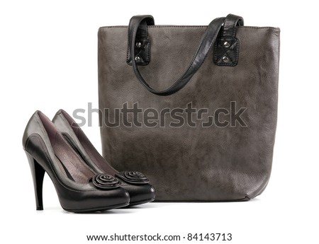 Pair of black female shoes and handbag over white - stock photo