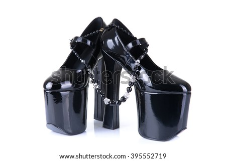 Pair of black fetish shoes with bead necklace, isolated on white background