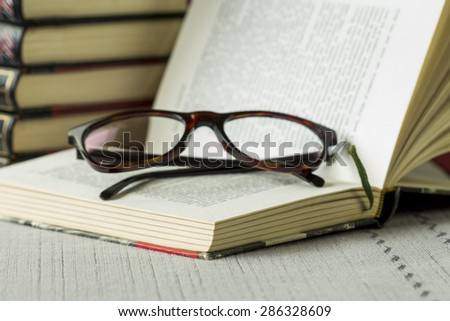 Pair of black framed reading glasses on an open book lying on a table with tablecloth in front of a stack of leather bound retro hardcover volumes