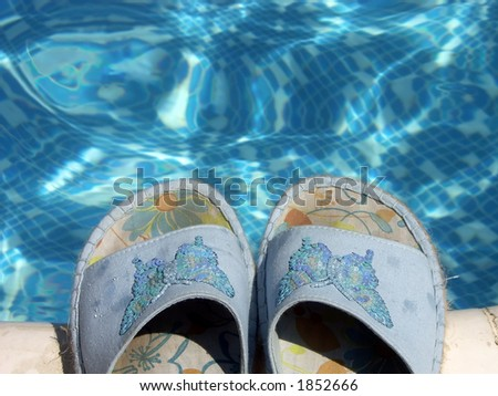 Pair of blue flip-flops by the swimming pool