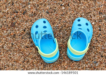 "Pair of blue slippers ""Crocs"" on the sand"