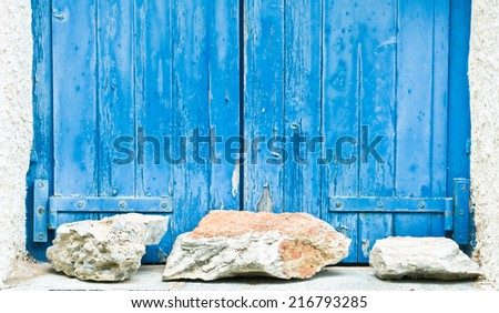 Pair of blue window shutters protected by rocks - stock photo