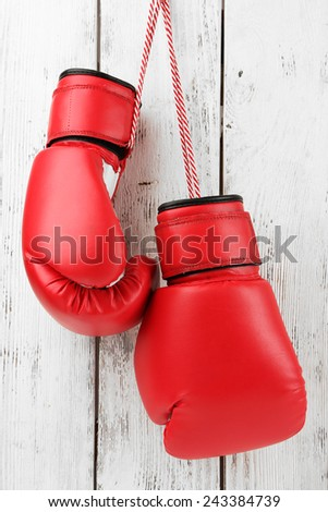 Pair of boxing gloves on color wooden background - stock photo