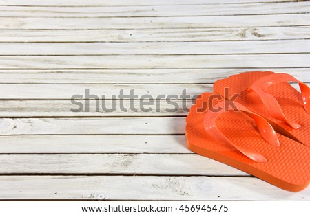 pair of bright orange flip-flops on wooden whitewashed deck - stock photo
