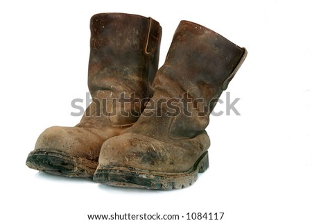 Pair of brown leather well worn  steel toe capped builders boots, covered in mud and paint splatters. - stock photo