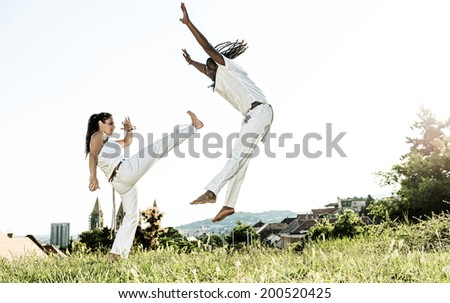 Pair of capoeira performers doing a kicking - stock photo