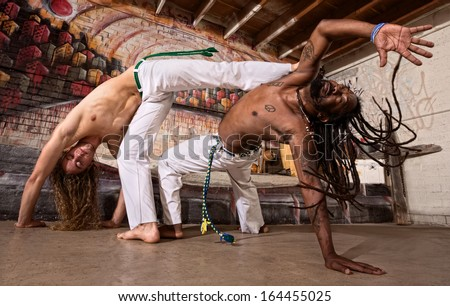 Pair of capoeira performers doing a kicking demonstration - stock photo