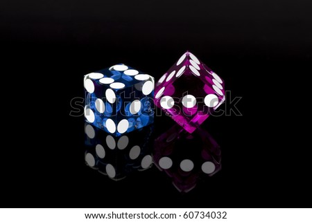 Pair of casino gaming/gambling dice isolated on a black background with reflection. - stock photo