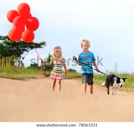 pair of caucasian siblings walks along a sandy path with their pet dog and a bunch of red balloons