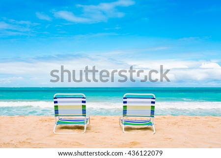 Pair of chairs on a beautiful white sand beach. Location Hawaii. - stock photo