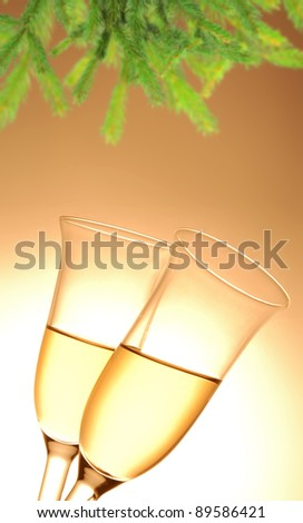 Pair of champagne flutes and Christmas decoration on orange background - stock photo