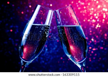 pair of champagne flutes with gold bubbles make cheers on blue tint light bokeh background - stock photo