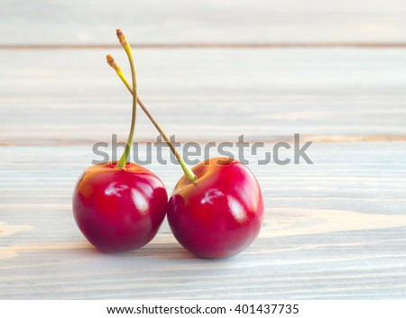Pair of cherries on wooden table. - stock photo