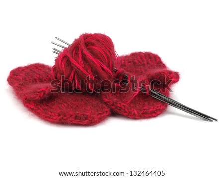 Pair of children's mittens, needles and wool ball on a white background - stock photo