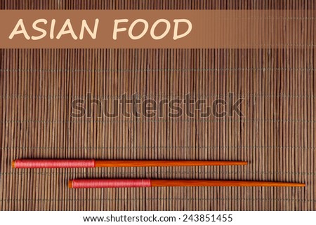 Pair of chopsticks and Asian Food text on brown bamboo mat background - stock photo