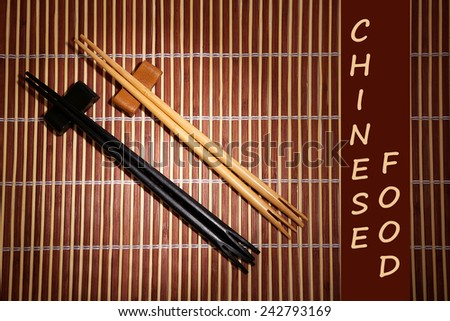 Pair of chopsticks and Chinese Food text on brown bamboo mat background - stock photo