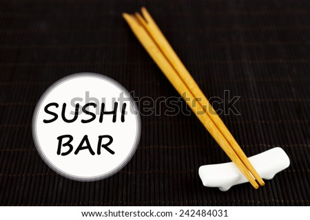 Pair of chopsticks and Sushi Bar text on black bamboo mat background - stock photo