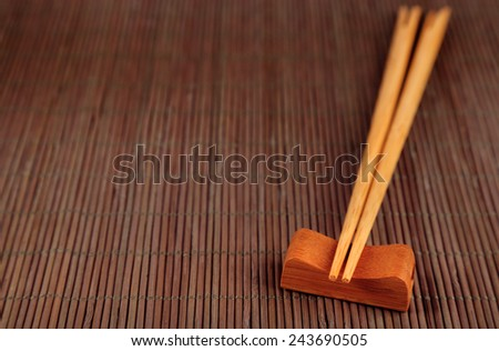 Pair of chopsticks on bamboo mat background - stock photo