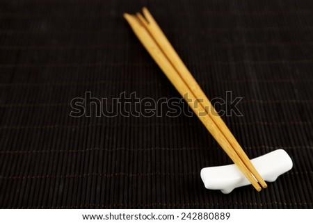 Pair of chopsticks on black bamboo mat background - stock photo