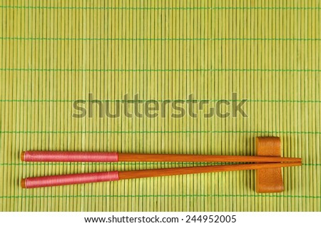 Pair of chopsticks on green bamboo mat background - stock photo